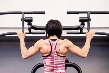 Vältränad kvinna gör pull-ups på gym